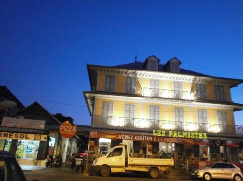 View across a street to Les Palmistes restaurant. Evening.
