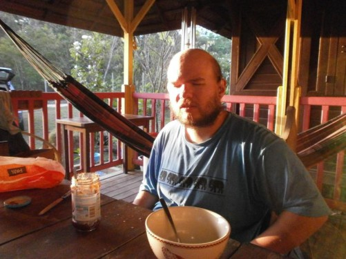 Tony sitting at a table on the verandaeating breakfast.