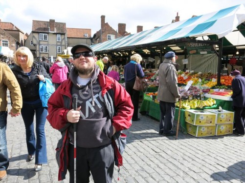Tony at the market in the centre of York. Food stalls in view.