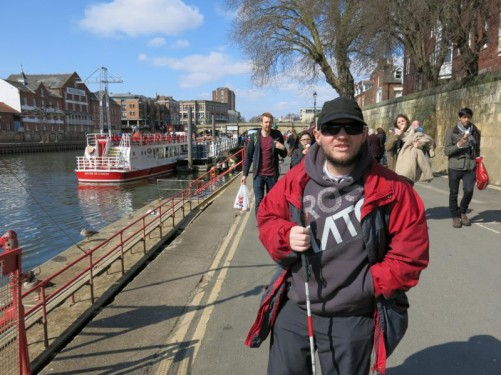 Tony on a street by the River Ouse in the centre of York. A boat offering river cruises moored along side.