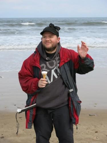 Tony eating an ice cream on the beach.