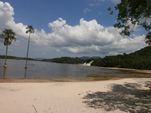 View of Canaima lagoon from a sandy beach. Looking along the densely wooded edge of the lagoon, Salto Ucaima, the nearest waterfall to Canaima Village, can be seen in the middle distance.