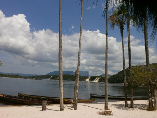 Another vista from the beach. In the foreground trees growing on the beach and wooden canoes tied up on the shore. Along the side of the lagoon, four separate waterfalls can be seen: from nearest to furthest they are called Salto Ucaima, Salto Golondrima, Salto Wadaima and Salto Hacha.
