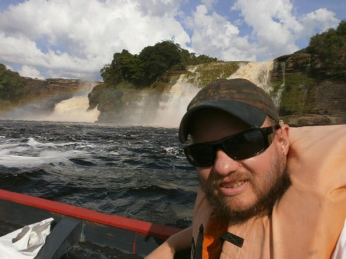 Tony in the canoe as it passes in front of Ucaima and Golondrima waterfalls. Rainbow again visible.