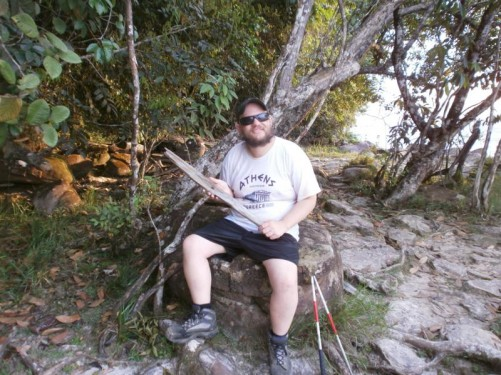 Tony sitting on a rock holding a piece of weathered wood. Trees and bushes behind. Near the beach at Isla Anatoly again.