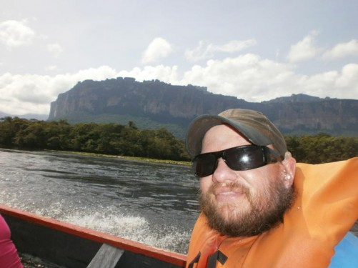 In the motorised canoe on the Carrao River at this point heading to Angel Falls. The boat ride took over five hours due to the shallowness of the rivers. Forest along the shore with massive rocky cliffs towering inland.