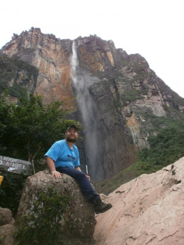 Tony sitting on a boulder, Angel Falls plunging down the sheer side of the mountain behind him.