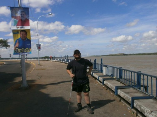 Tony by the wide Orinoco River. It is about 1 mile (1.6 km) wide at this point. A large suspension bridge over the river can be seen away in the distance.