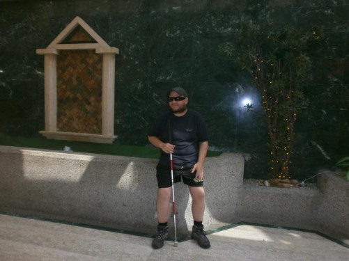 Tony leaning against a marble wall. Alongside is a plant with a string of small lights wrapped around its stems. Probably inside the cathedral.