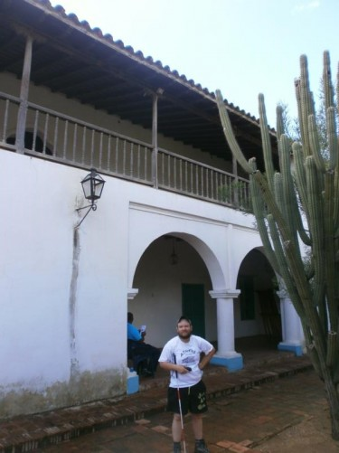 Tony outside a white-painted colonial-era house. A tall cactus also in view.