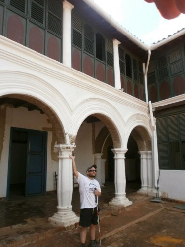 The inner courtyard of the Coro Art Museum. Tony in front of the stone column of a covered walkway that runs along one side.