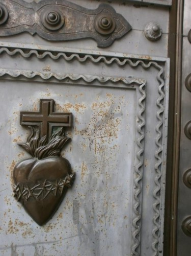 Detail on a metal door into the cathedral: a heart surrounded by a ring of thorns, with a cross standing above.