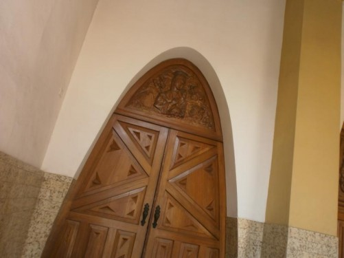 Arched wooden doorway into the church.
