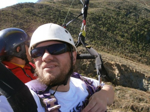 Tony strapped into a harness with his pilot as he begins his paraglide.