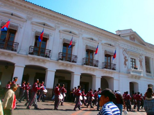 The military band marching past. The men are dressed in red jackets and black berets. Those immediately in front are banging drums.