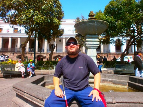 Tony sitting on the side of a fountain in Independence Square.