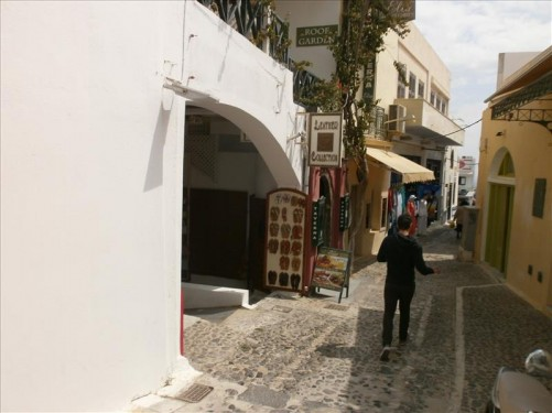 View down a narrow street with cobble stones under foot. Shops and restaurants.