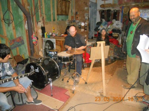 Tony playing drums inside the house where the sculptures are located. The local kids practice their music there. A boy is sitting at the side holding a guitar.