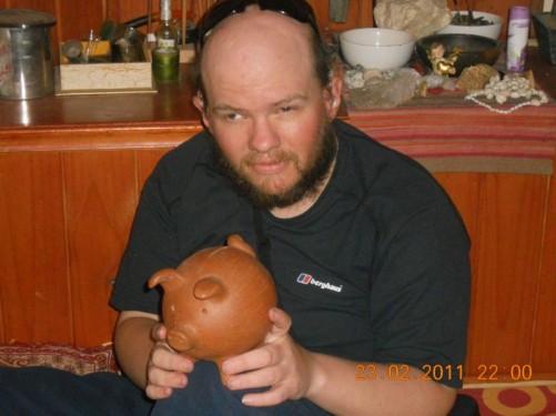 Tony holding a wooden piggy bank.