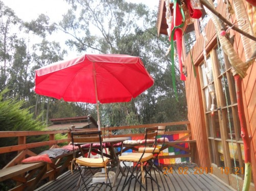 A patio area outside the hostel. A table and chairs with a sun umbrella in front.