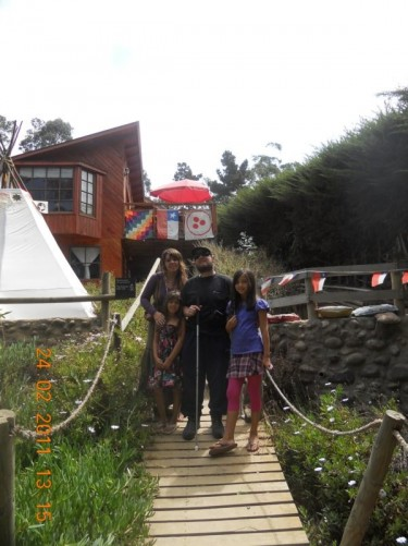 Tony with Sandra and two girls on a small wooden bridge in front of the hostel.