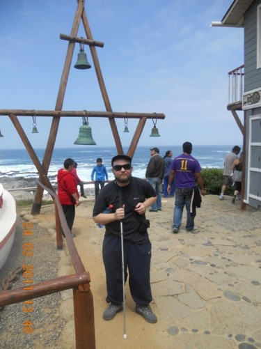 Tony in front of a number of bells of different sizes, which are hanging from a framework of wooden beams. The sea can be seen behind.