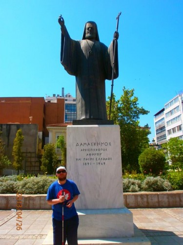 Tony by a statue of Archbishop Damaskinos, the Archbishop of Athens during World War II. It is located in the square in front of the Metropolitan Cathedral of Athens.