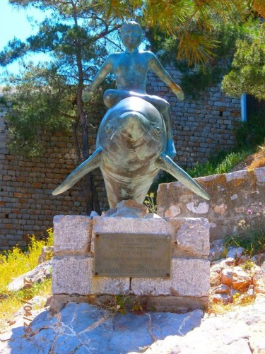 Bronze sculpture of a boy sitting on a dolphin. This was inspired by the 1957 Hollywood film 'Boy on a Dolphin', which was shot on Hydra and other Saronic Islands.