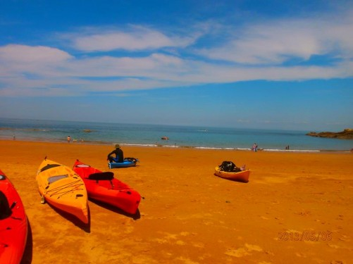 Looking towards the sea. A number of canoes on the sand in front.