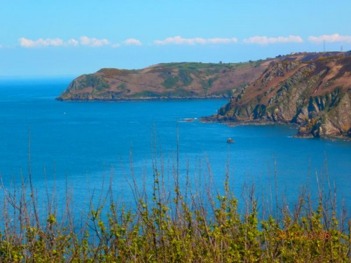 View along Jersey's north coast. Probably Bonne Nuit Bay in the foreground and Giffard Bay beyond. Rocky cliffs along the coast.