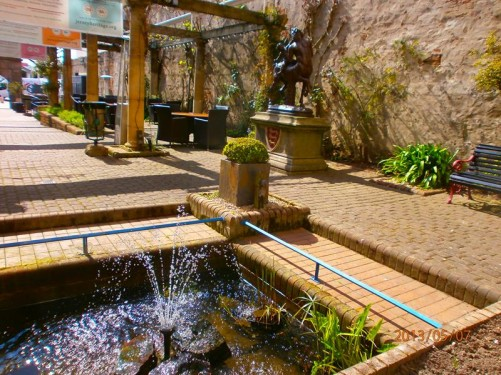 A pedestrian area outside Jersey Museum and Art Gallery. A fountain in front and a bronze statue of a centaur ridden by Eros just visible to the right.