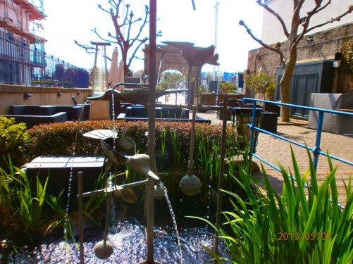 Still outside Jersey Museum and Art Gallery: a pond with plants and a water feature that includes metal birds with water coming out of their mouths. A seating area beyond.
