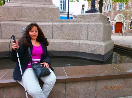 Tatiana sitting at the side of a fountain.