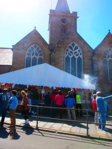 A stall selling food at the side of the church. Part of the Liberation Day festivities.