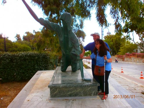Tony and Tatiana both touching a metallic statue of a female pilgrim crawling on her hands and knees, near the church.