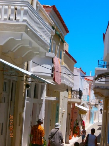 A pedestrian street running through Andros Town (Hora). The buildings painted in pastel shades of yellow, red and blue, as well as the traditional white. Balconies above.