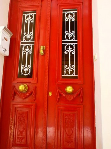 An attractive door to a house: it is red, with wood-carved decoration and metal work over two rectangular windows.