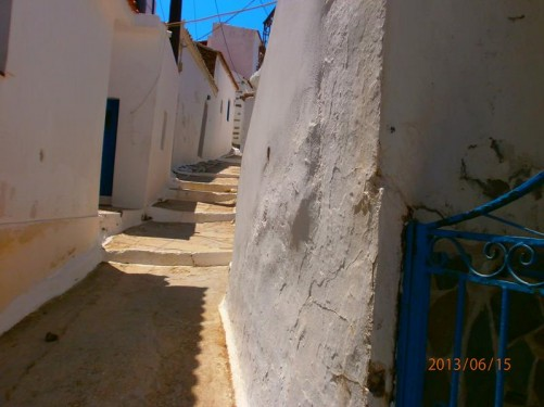 Quiet narrow back street lined with white walls. A few steps heading up hill in front.
