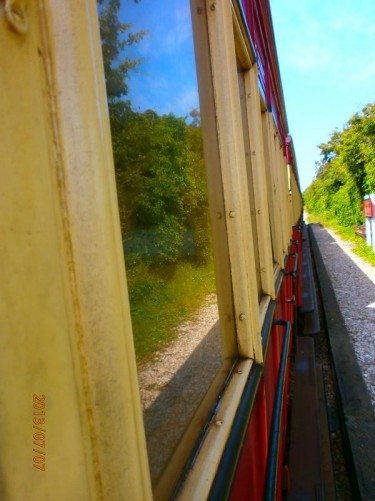 View down the side of the red and cream coloured railway carriages.