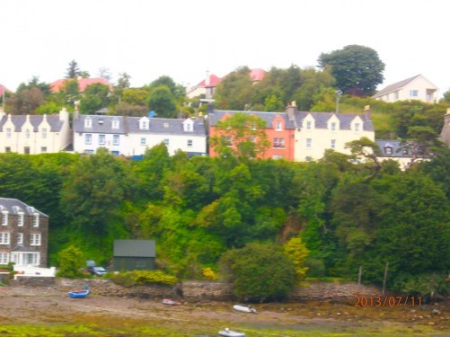 Looking from Portree harbour to a row of houses in the town above.