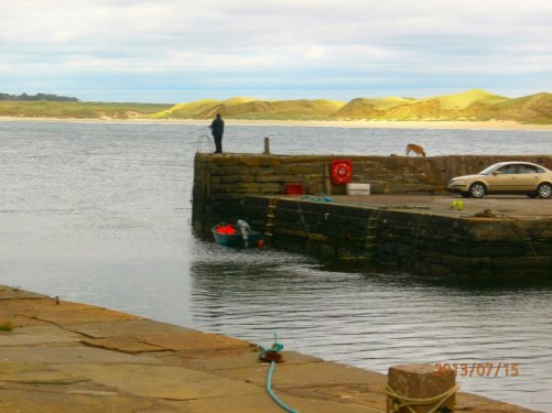 The small harbour at John O'Groats. A man fishing from the harbour wall. John O'Groats is on the north-eastern tip of Scotland.