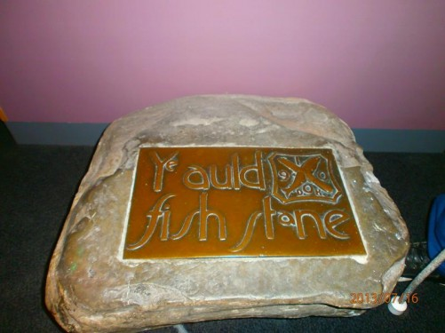 An old looking stone with an attached metal plaque that reads 'Ye auld fish stane'. This stone stood in Thurso market place from the 1850s to the 1970s and marks the spot where fishwives traditionally gathered to sell their fish. It is now kept in Caithness Horizons museum in Thurso.