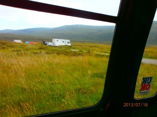 View of grassy moorland from the window of a coach heading to Lyness, the island's capital. Approaching a few cars and camper vans parked off the road.