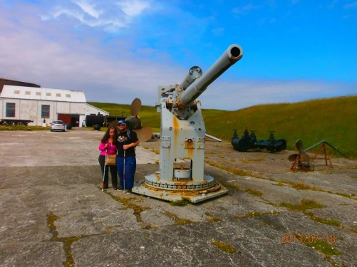 Tony and Tatiana at Scapa Flow Museum in Lyness. They are standing by a large rotating gun, probably originally mounted on a ship.