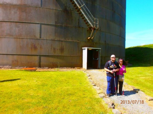 In front of a large metal cylindrical building, originally an oil storage tank, now part of the museum.