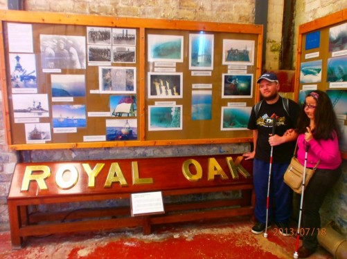 Inside the museum. Tony and Tatiana by the name plate for the HMS Royal Oak. An information board above.