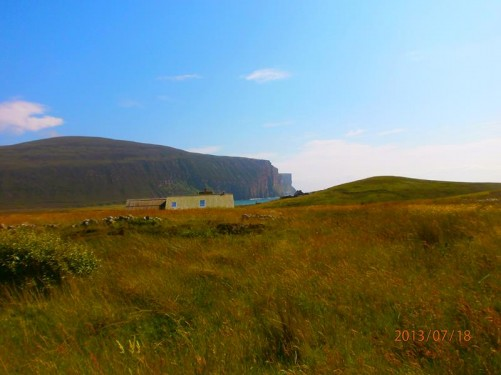View across grassland towards a cottage. Further away, Rackwick Bay, with very high towering cliffs of its far side.