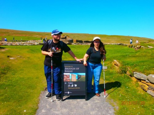 Tony and Tatiana by a 'Welcome to Brough of Birsay' board. Ruins of stone buildings in the background.
