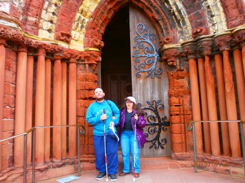 Tony and Tatiana outside the weathered red sandstone doorway of St Magnus' Cathedral.