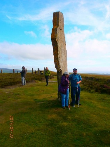 Tatiana and Tony in front of a tall standing stone at the Ring of Brodgar. The ring originally comprised 60 stones, of which only 27 remain today.